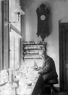 An old, bespectacled man wearing a suit and sitting at a bench by a large window. The bench is covered with small bottles and test tubes. On the wall behind him is a large old-fashioned clock below frick u which are four small enclosed shelves on which sit many neatly labelled bottles.