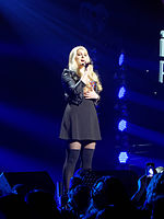 A young blonde woman singing into a microphone onstage, sporting a black skirt and black Bad Gal jacket. Blue stage lights shine upon her, while the logo of iHeart Radio serves as her backdrop.