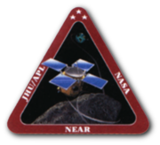 "An artwork of a spacecraft hovering above an asteroid, enclosed in an equilateral triangle with thick, red border. The words ""JHU/APL"", ""NASA"", and ""NEAR"" are printed in bold white font, on the left, right, and bottom sides of the triangle's borders."