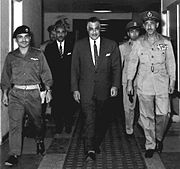 Three important men walking in a hall, the first and the third are in military garb, the second is in a suit and tie. Behind them are three other men