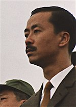 Middle-aged man with side-parted black hair and moustache, in a black suit, white shirt and brown tie. To the left is a clean-shaven Asian man with black hair and a green military cap.