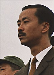 A middle-aged man with side-parted black hair and a moustache, in a black suit, white shirt and brown tie. To the left is a clean-shaven Asian man with black hair and a green military cap.