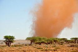 Une colonne d'air surchargée de sable rouge s'échappe d'une nappe plus basse d'air charge de sable