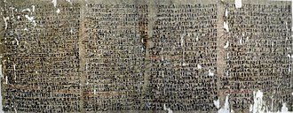 Large papyrus full of cursive inscriptions in black and occasional red ink, riddled with small holes.