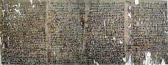 Image of a dark papyrus covered with writings in black ink and scattered holes