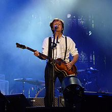 McCartney on stage playing guitar and singing.