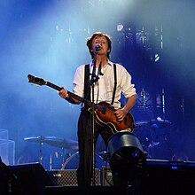 McCartney no palco tocando violão e cantando.