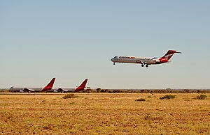 Alice Springs Airport - A QantasLink Boeing 717 landing with the boneyard in the background