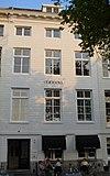 foto van Koopmanshuis, met gebosseerde, natuurstenen lijstgevel, waarin een jaartal. Brede cordonlijst boven de onderpui