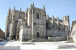 Une église massive en pierre blanche. Les murs sont prolongés par des murets décoratifs qui masques la forme du toit.
