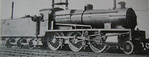 Side-and-front view of a 3-cylinder 2-6-0. The distinguishing feature is a full-width flat panel rising vertically above the front buffer beam to the level of the bottom of the smokebox door.