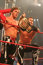 Two male wrestlers standing in a ring holding championship belts wearing black wrestling gear.