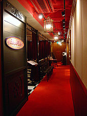 A view through a doorway into a cafe area; a sign reads Sakura Cafe and the interior is decorated using wood panelling with red and gold elements.