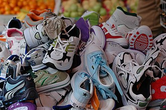 Sneakers - A large pile of low-quality athletic shoes for sale at a market in Hong Kong