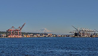 Mount Rainier - Mount Rainier behind the Starbucks corporate HQ clock tower in Seattle, as seen from the Bainbridge Island ferry, with Port of Seattle cranes