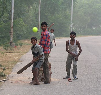 English: Four Indian boys playing cricket in t...