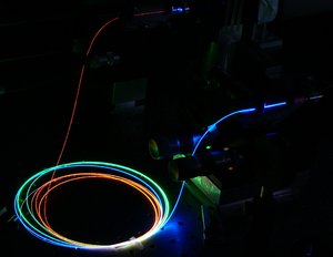 Supercontinuum - Propagation of ultrashort laser pulses in a microstructured optical fiber. The input laser light (bottom of the picture, not visible before entry into the fiber) is near infrared and generates wavelengths covering most of the visible spectrum.