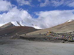 Gravel road through high mountains with brightly coloured prayer flags at the side