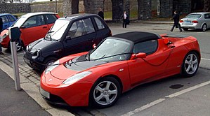 A Tesla Roadster and other electric cars parke...