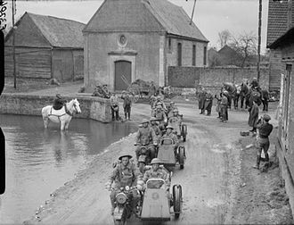 50th (Northumbrian) Infantry Division - Motorcycle combinations of the 4th Battalion, Royal Northumberland Fusiliers pass through a village, watched by the local inhabitants, France, 20 March 1940.