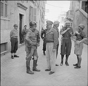 John Hawkesworth (British Army officer) - General Sir Harold Alexander with Major General Lucian Truscott and other senior Allied commanders at Anzio, Italy, 5 May 1944. Hawkesworth is pictured on the far right wearing a Parachutist Helmet, and to the left of him is Major General Philip Gregson-Ellis.