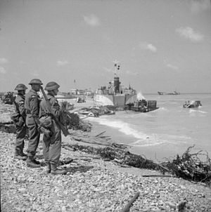 Beach groups - Beach Group troops look out from Queen beach, Sword, littered with beached landing craft and wrecked vehicles and equipment, 7 June 1944