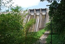 Large gray concrete dam, viewed from below