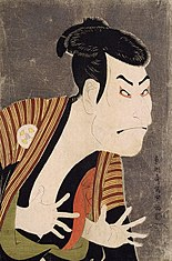 Colour print of a colourfully made-up Japanese actor making a bold expression with his fingers extended, facing right.