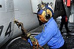 U.S. Navy Airman Lafreya Skipperwright secures an MH-60S Seahawk helicopter assigned to Helicopter Maritime Strike Squadron (HSM) 74 to the deck in the hangar bay of the aircraft carrier USS Harry S. Truman (CVN 131008-N-LH273-017.jpg