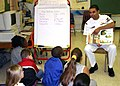 US Navy 040416-N-8102J-004 Aviation Warfare Systems Operator 2nd Class Mario Gomez reads to students.jpg