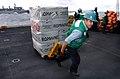 US Navy 040623-N-6213R-004 Storekeeper Seaman Arthur Valdez, from Houston, Texas, pulls a pallet of supplies into the hangar bay.jpg