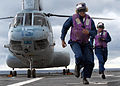 US Navy 070612-N-5067K-113 Aviation Boatswain's Mate (Fuel) Airman Robert D. Cunningham and Aviation Boatswain's Mate (Fuel) Airman Joan R. Abreu hurry as a Marine CH-46 Sea Knight prepares to take off from amphibious transport.jpg