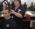 US Navy 070702-N-0847K-027 A student with Officer Candidate School (OCS) Class 20-07 receives his first Navy haircut from Pamela Pendergrast, a barber with the Navy Exchange on board Naval Air Station (NAS) Pensacola.jpg