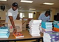 US Navy 070808-N-7427G-005 Information Systems Technician 1st Class Horace Wesley and Yeoman 3rd Class Tony Clofer organize books for the Belle Chasse Academy Charter School.jpg