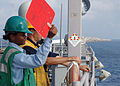 US Navy 080729-N-9134V-102 Seaman Noelle Gilchrist uses a signal paddle during a replenishment at sea.jpg