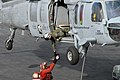 US Navy 081114-N-9132C-082 An aircrewman leans out of an MH-60S Sea Hawk.jpg