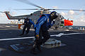 US Navy 091006-N-1688B-427 Sailors remove the chocks and chains from a British Royal Navy Lynx helicopter and clear the flight area aboard the guided-missile destroyer USS Cole (DDG 67).jpg