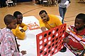US Navy 091007-N-6220J-009 Damage Controlman 3rd Class Ricardo Nesmith, left, and Yoeman Dennis Armstrong, assigned to Navy Operational Support Center, Greenville, play the Battleship game with two boys.jpg