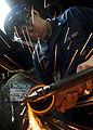 US Navy 111011-N-BT887-330 Hull Maintenance Technician 3rd Class Jeffrey Meginness, from Modesto, Calif., grinds a hatch stanchion aboard the Nimit.jpg