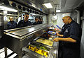 US Navy 111020-N-RB564-037 Culinary Specialist 1st Class David Gonzales serves the crew.jpg