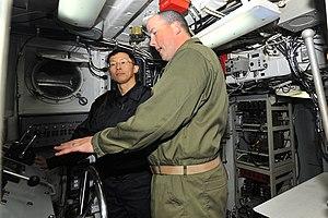 US Navy 120212-N-KB563-083 Chief Operations Specialist Barnett gives Rear Adm. Kitagawa Fumiyuki a tour of Landing Craft Utility (LCU) 1632.jpg