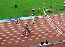 Eight men approach the finishing line of race at a stadium track