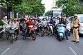 Vietnamese Motorbike Riders Pause as Secretary Kerry Crosses Street (11372986094).jpg