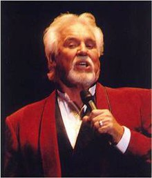 A man with a gray mustache, beard, and hair, wearing a red jacket and singing into a microphone