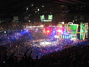 A sold out crowd watching the event, with a professional wrestling ring in the center of the picture. A giant screen in the shape of a briefcase is at the top right.