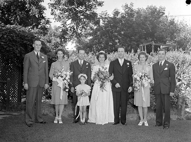 """""""Nous voyons les nouveaux mariés Ruth Schnebly et John Roland avec les filles d'honneur, les garçons d'honneur et la petite bouquetière. Ils sont debout dans un jardin."""" by Conrad Poirier"""
