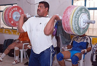 Weight plate - A weightlifter holding an Olympic barbell loaded with plates ranging from 5 to 25 kilograms