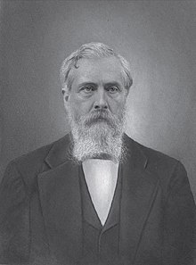 A man with white hair and a white beard and mustache wearing a white shirt, black jacket and black vest