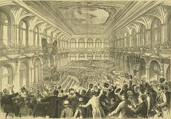 Black-and-white drawing of a vast assembly hall, viewed from the back of a left-side gallery. Far below (barely discernible) other delegates are gathered around the grand stage to our left. Closer, we see the backs of many men in long coats, most standing in excitement, holding or waving their top hats and bowlers.
