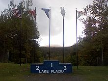 Un podium portant l'inscription « Lake Placid » devant cinq drapeaux.